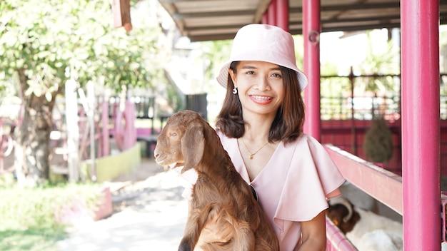 タイの観光客は写真撮影のために赤ちゃんヤギを喜んで抱きます