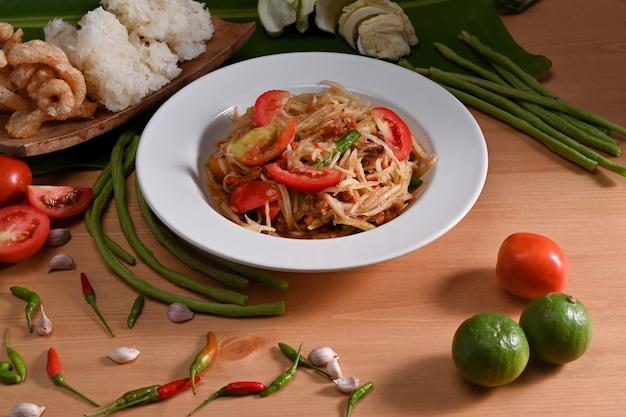 Тайская традиционная еда. зеленый салат из папайи и ингредиенты на деревянном столе.