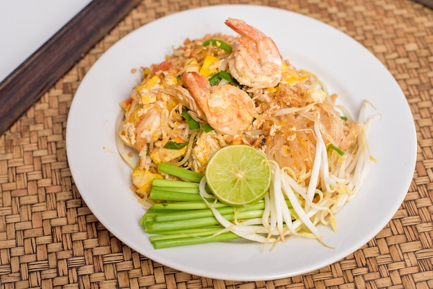 タイの伝統的な食べ物パッタイ麺とエビの皿に木製のテーブル