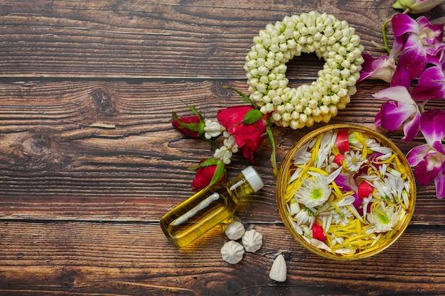 タイの伝統的なジャスミンの花輪と水入れのカラフルな花の装飾と香水、マーリー石灰岩