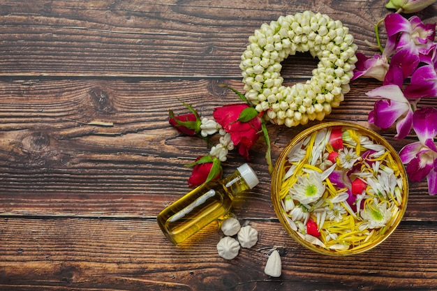Thai traditional jasmine garland and colorful flower in water bowls decorating and perfume, marly limestone