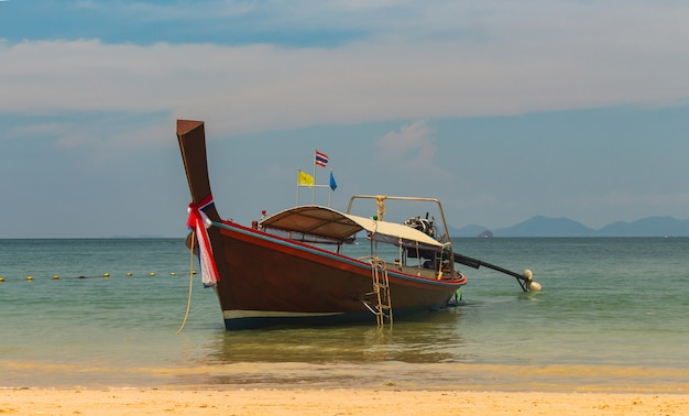 Thai traditional wooden long tail boat and stone mountain is located at the beautiful sea.