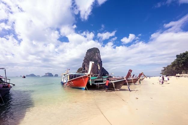 タイの伝統的な木製ロングテールボートとクラビ県の美しい砂浜洞窟山