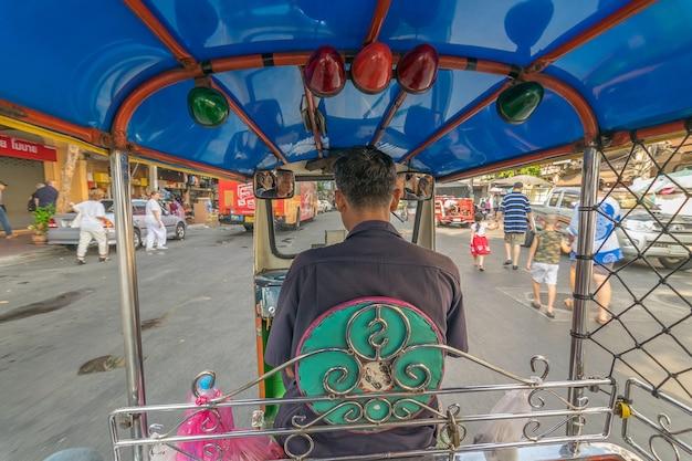 Thai tuktuk taxi running on the road in bangkok, thailand.