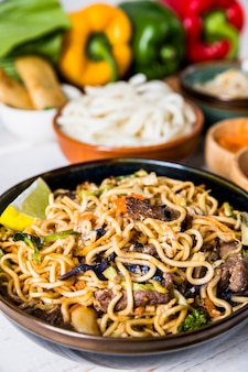 Thai udon noodles with beef and slice of lemon