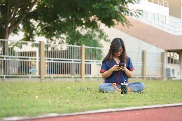 携帯電話にはまっているタイの女性