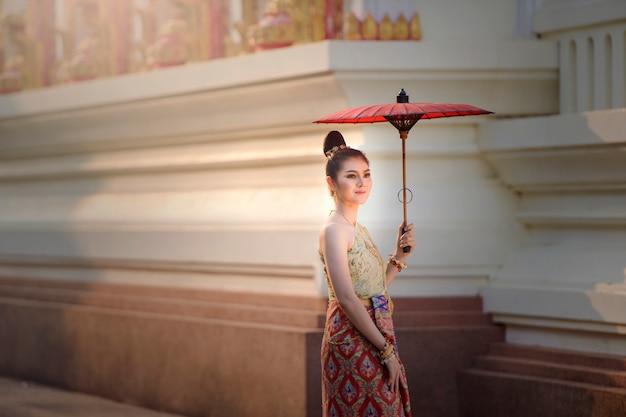 伝統的な衣装でタイの女性。伝統的なタイの文化、ヴィンテージスタイル、タイを身に着けているアジアの美しい女性