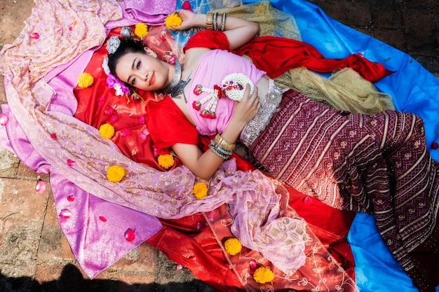 Thai woman wearing thai traditional clothing lie down on silk of various colors.