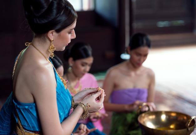 アユタヤ王朝時代の古代の衣装を着たタイの女性古い家でタイの甘い食べ物と一緒に