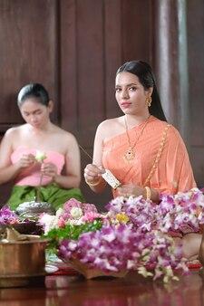 Тайские женщины в традиционной тайской одежде украшают цветы.