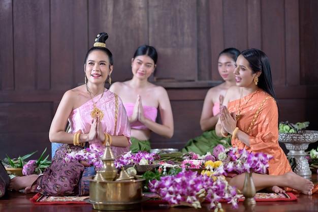 タイの伝統的な衣装を着たタイの女性が花を飾っています。