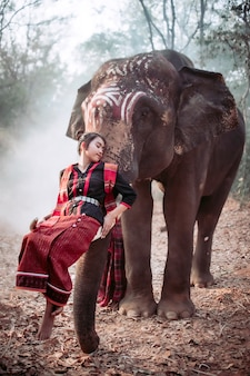 Thai women in national costumes standing with a red umbrella, watching the thai elephant in front of her