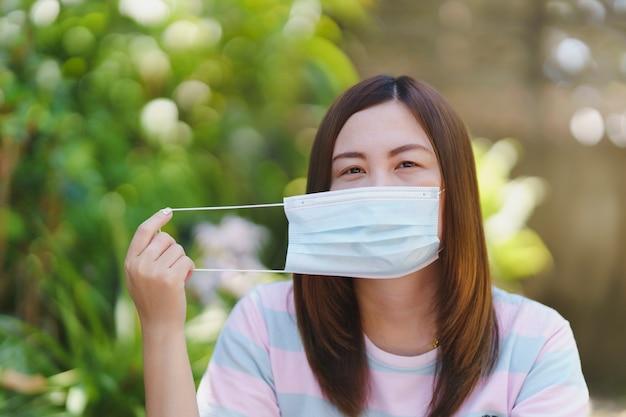 自然なぼかしの背景を持つマスクを身に着けているタイの女性。病気の予防のための概念。