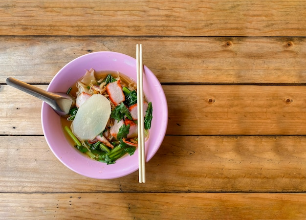 木製のテーブル背景にタイの黄色い麺の食事。