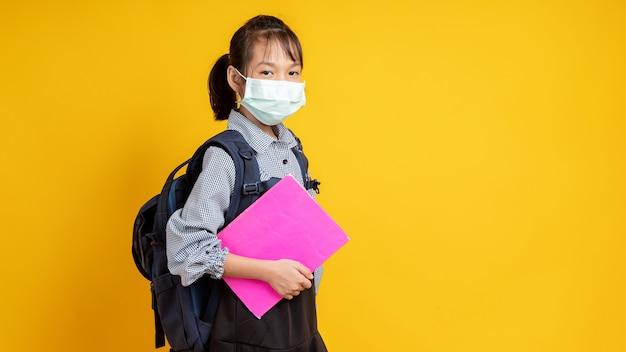 フェイスマスク、黄色またはオレンジに分離された本を保持しているアジアの子供を着てタイの少女