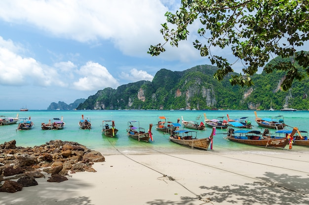 Thailand beach seascape with  steep limestone hills and traditional longtail boats parking
