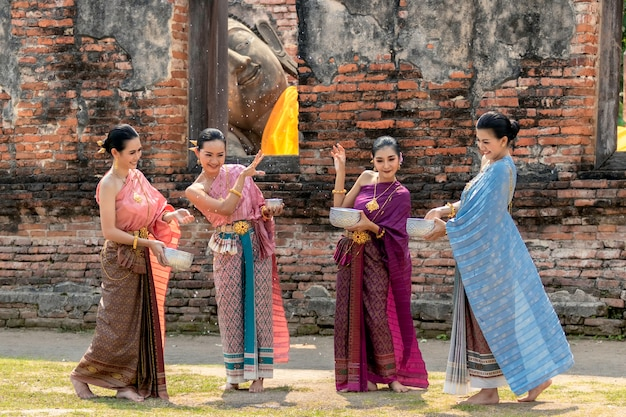 Thailand culture. thai girls and thai women playing splashing water during with thai traditional costume in the temple of ayutthaya thailand festival songkran festival.