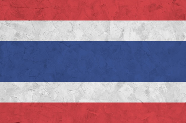 Thailand flag depicted in bright paint colors on old relief plastering wall. textured banner on rough background