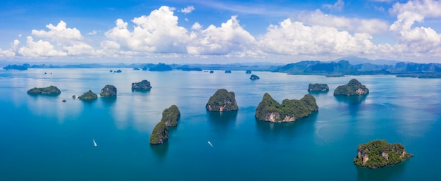 Thailand green lush tropical island in a blue and turquoise sea with islands in the background and clouds
