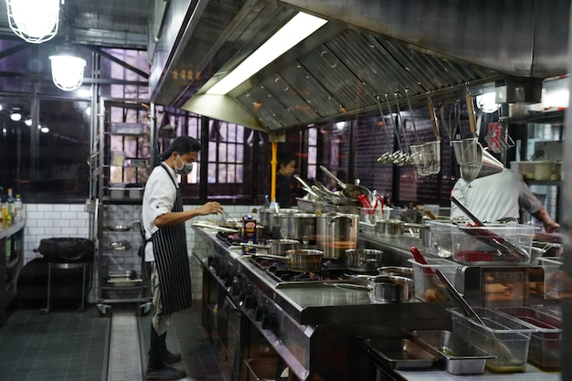 Thailand - october 10,2018 : 2 assiant chefs cook the food in open kitchen restaurant.
