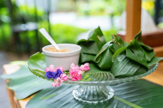 Традиционный тайский десерт в обертке из банановых листьев на стеклянном блюде есть с сахаром рядом с ним. обустройство на деревянном столе в открытом саду.