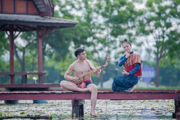 Thailand women and man in national costume with guitar pin ( plucked stringed instrument)