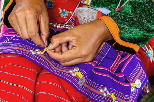 Thailander hill族の女性のクローズアップ手は、彼女の村の観光客のための衣装の縫製と装飾を示しています。