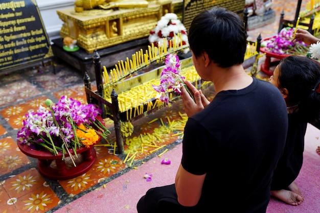 Таис буддист делает заслугу в храме.