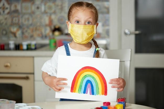 Nhsに感謝します。 covid-19検疫中に自宅で虹を描いている防護マスクの子供。コロナウイルスcovid-19の発生。