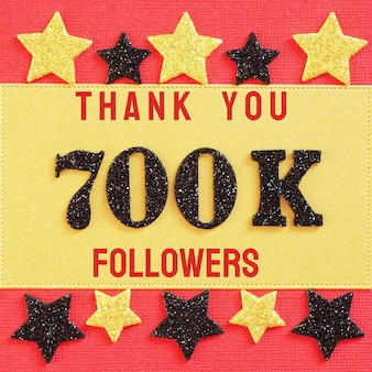 Thank you 700k, 700000 followers. message with black shiny numbers on red and gold