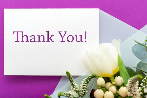 Thank you card in bouquet of roses, tulips, eucalyptus on purple surface