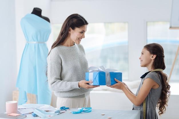 Спасибо, дорогой. радостная милая молодая женщина смотрит на свою дочь и улыбается, получая от нее подарок