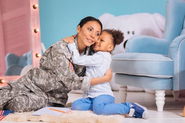 Спасибо за помощь мне. красивая очаровательная любящая дочь обнимает свою мать и выглядит счастливой после того, как закончила домашнее задание раньше, чем обычно