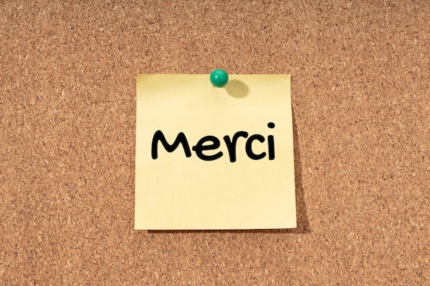Thank you in french written on yellow post it on corck board background