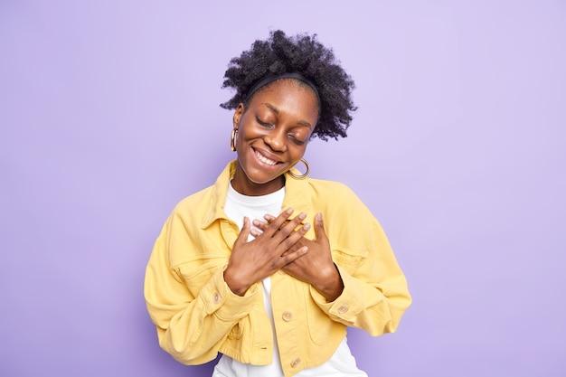 진심으로 감사드립니다. 기뻐하는 흑인 여성이 감사하는 몸짓으로 무언가를 감상하게 합니다.