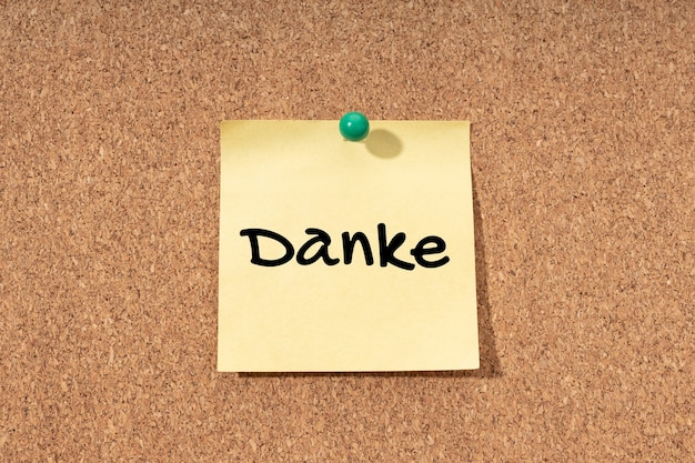 Thank you in german written on yellow post it on corck board background