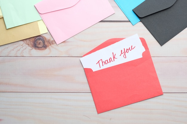 ありがとうメッセージと木製のテーブル上の封筒