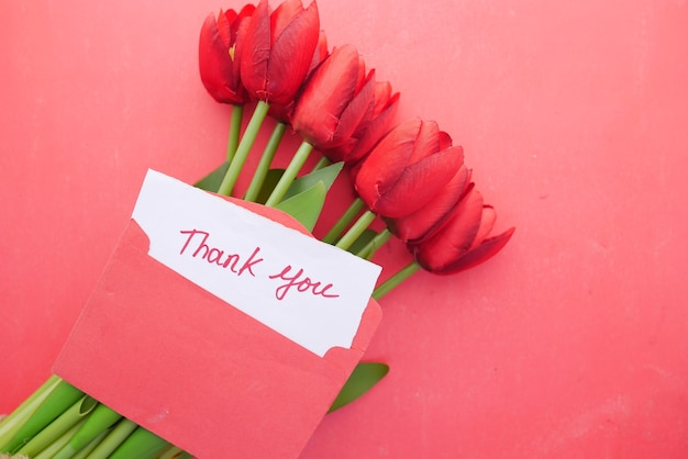 감사 메시지 봉투 o와 ted 표면에 빨간 튤립 꽃