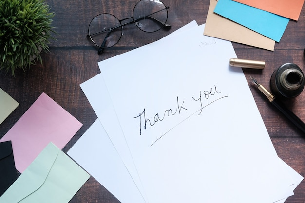 Thank you message and envelope on wooden table