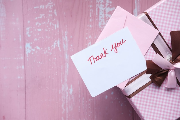 Thank you message and gift box on pink space .