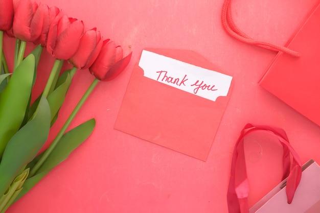 赤にチューリップの花が付いた紙にメッセージをありがとう