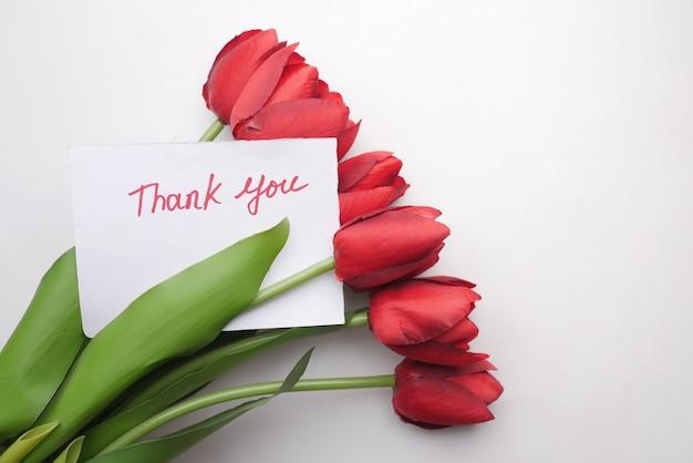 白い背景の上のチューリップの花と紙にメッセージをありがとう