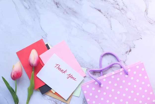Thank you message on a paper note tulip flower on tiles space .