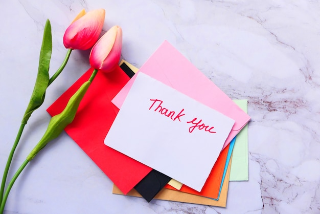 Thank you message on paper with tulip flower