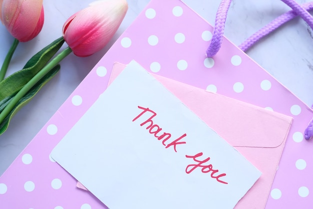 Thank you message on sticky note with tulip flower on pink background.