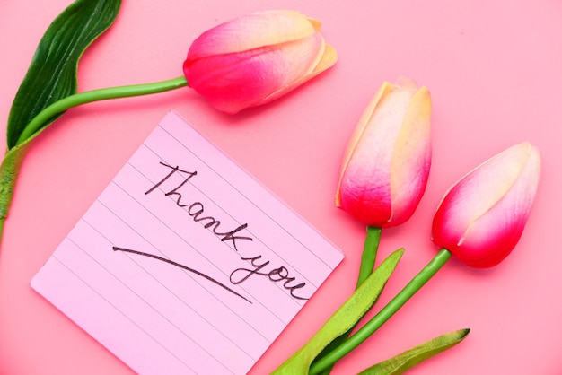 Thank you message on sticky note with tulip flower on pink background