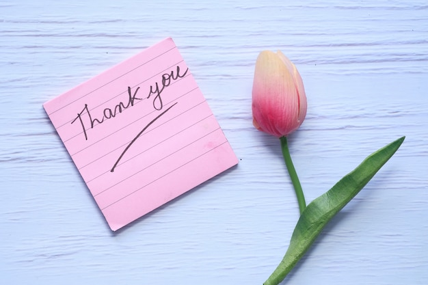Thank you message on sticky note with tulip flower on white background