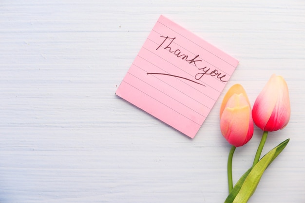 Thank you message on sticky note with tulip flower on white space .