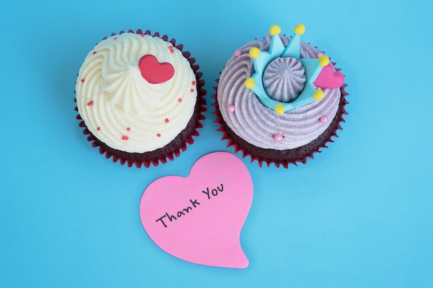Thank you note in heart shape paper with two cupcake