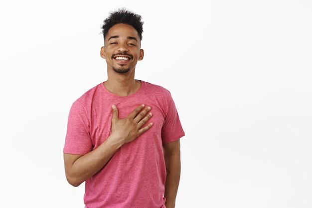 Grazie. sorridente uomo afroamericano che sembra orgoglioso e felice, compiaciuto di smth, tenendo la mano sul cuore con gratitudine, si presenta, in piedi in maglietta rosa su bianco